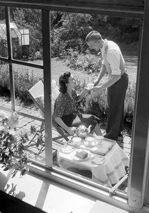 Couple taking afternoon tea in the garden, 1951.