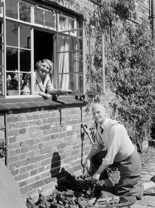 Man gardening as a woman looks on from a window, 1953.