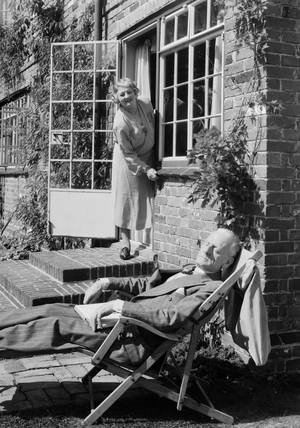 Woman calling to an elderly man asleep in a deckchair, 1953.