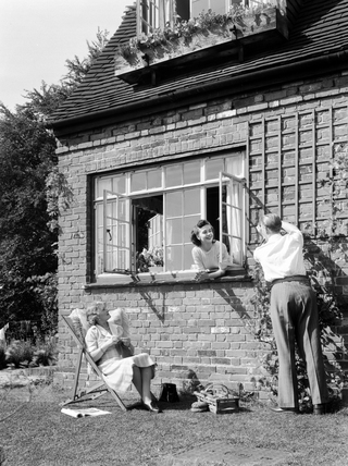 Man fixing a garden trellis, c 1950.