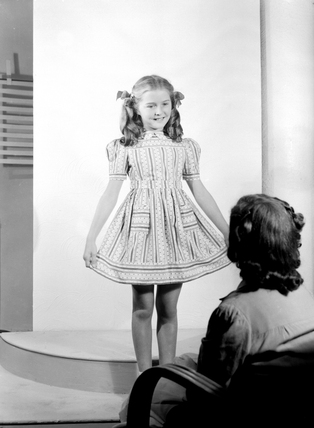 Little girl showing off her dress, 1952.