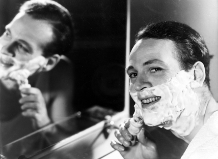 Man applying shaving foam to his face, c 1950s.