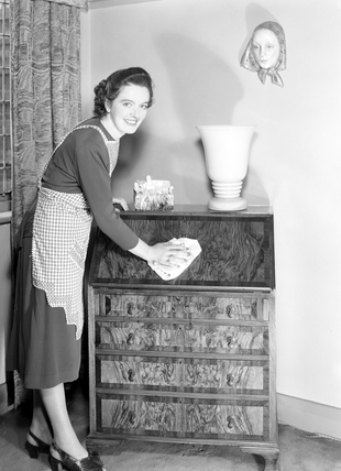 Woman polishing a chest of drawers, 1952.