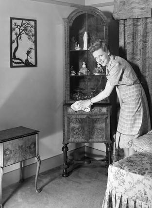 Woman polishing a cabinet, c 1950.