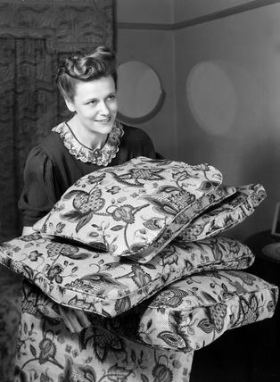 Woman carrying cushions, c 1948.