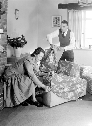Couple fitting armchair covers, 1949.