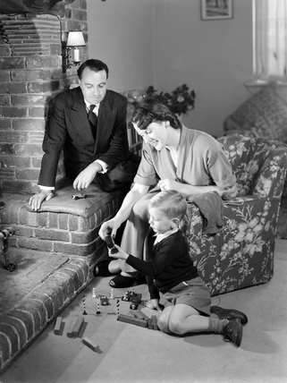 Little boy playing at the feet of his parents, 1952.