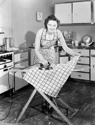 Woman ironing in the kitchen, late 1940s.