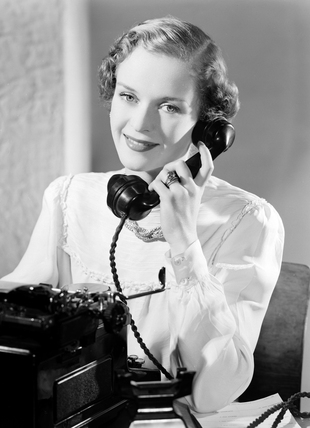 Typist answering the telephone, 1949.