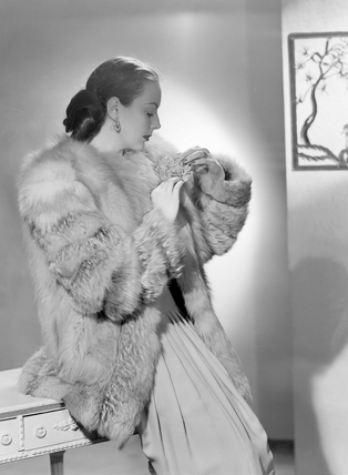 Woman wearing fur coat, c 1950