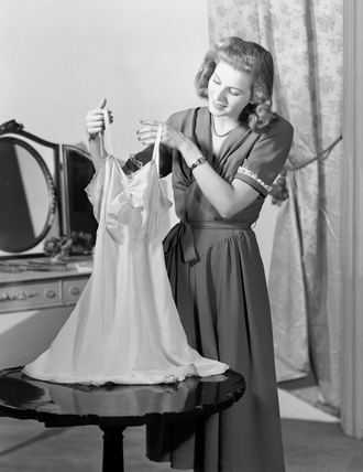 Woman in bedroom holding up a nightie, c 1930s.