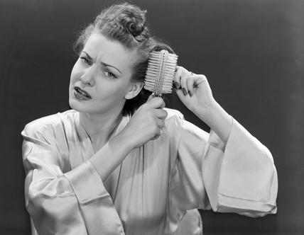 Woman brushing her hair, 1940-1955.
