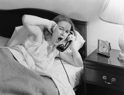 Yawning woman answering a telephone, c 1950.