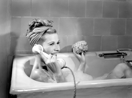 Woman lying in a foam bath answering a telephone call, c 1950s.