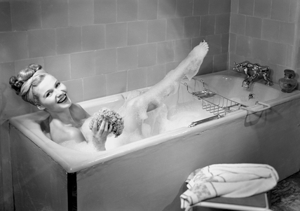 Woman lying in a foam bath with her leg out the water, c 1950s.