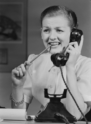 Woman answering a telephone, 1955.