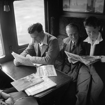 Two men and a boy sitting in a train carriage reading, 1950.