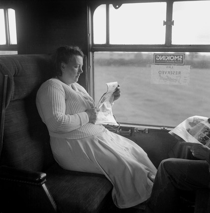 Woman reading a newspaper during her journey, 1950.