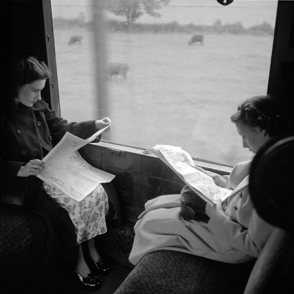 Women reading newspapers during their journey, 1950.