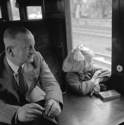 Father sitting with his daughter during a train journey, 1950.