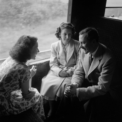Colin Wills of the BBC talking with two women during a train journey, 1950.
