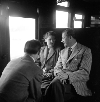 Colin Wills of the BBC talking with a man and a woman in a train carriage, 1950.