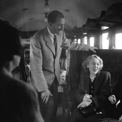 Colin Wills talking with a woman during a train journey, 1950.