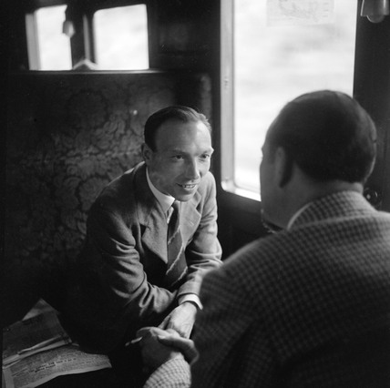 Colin Wills of the BBC talking with a man during a train journey, 1950.