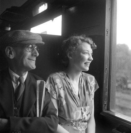 Elderly man and young woman looking out of carriage window, 1950.