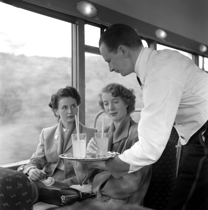 Waiter serving drinks to two female passengers, May 1953.