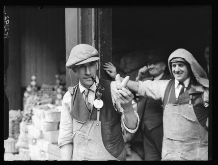 Man holding a carrot in the shape of a 'V' sign, c 1930s.