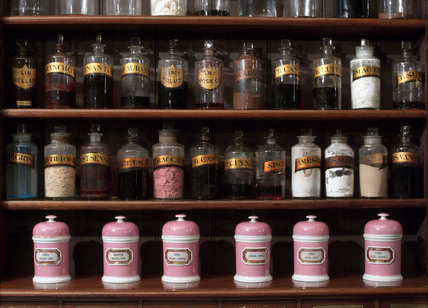 Shelves containing pharmaceutical bottles and jars, late 19th early 20th century.