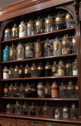 Shelves containing pharmaceutical bottles, late 19th early 20th century.
