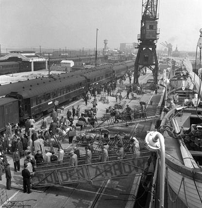 Passengers disembarking a ferry and boarding a train in the harbour, 1950.