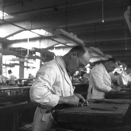 A clicker at work cutting out leather soles at a shoe factory. 1950.
