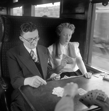 Passengers playing cards in a railway carriage, 1950.