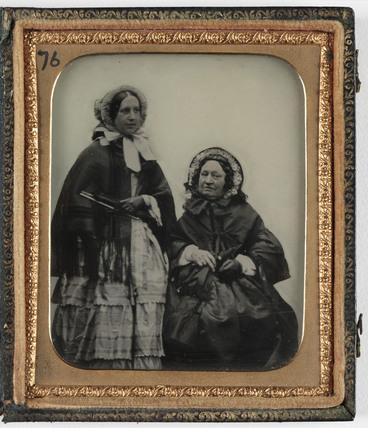 Two women in Victorian dress, c 1860.