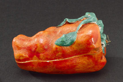 Porcelain red pepper containing a man and woman having sex.