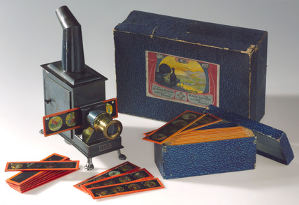 Child's magic lantern with twelve slides and original box, 1913-1920.