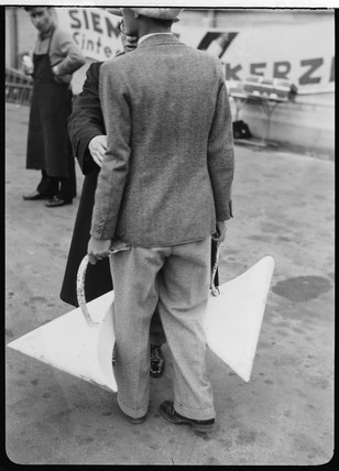 Man carrying two wheel fairings, Berlin, 1932.
