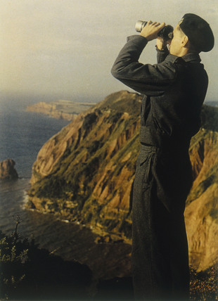 Soldier looking through binoculars on cliff tops, 1939-1945.