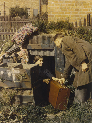 Man and woman with suitcase outside an anderson shelter, 1939-1945.