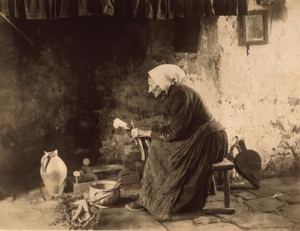 Woman preparing vegetables, c 1900.