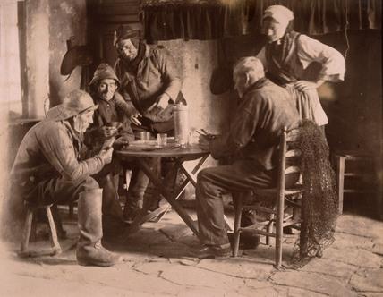 Men playing cards, c 1900.