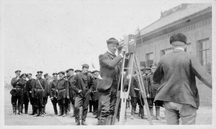Cameraman cranking a camera, c 1904.