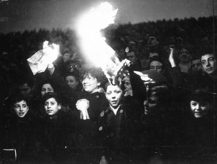 Spectators holding lit newspaper flares.