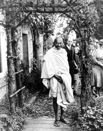 Mahatma Gandhi posing under a rustic arch, England, 1931.