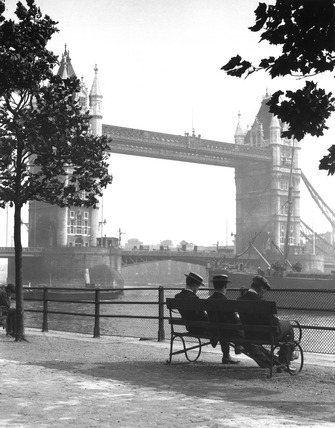 Men sitting by Tower Bridge on the River Thames, London, c 1920s.