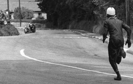 Sidecar passenger running on the track, TT race, Isle of Man, June 1960.
