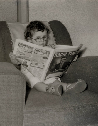 Small boy reading the 'Radio Times', 1950s.